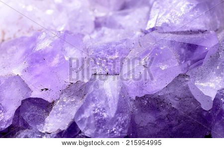 Closeup photograph of glittering translucent amethyst stone crystal with purple details. Natural phenomenon.