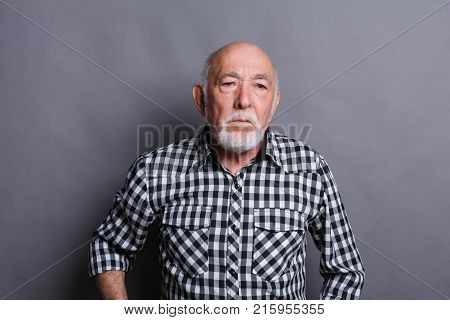 Mature man expressing disgust on face, grimacing on camera, gray studio background. Negative emotions, copy space