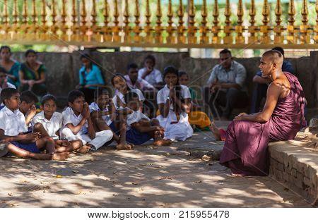 The Buddhist monk sitting under the shade of a big bodhi-tree tells school students about Buddha's doctrine. Seruwawila Mangala Maha Seya Sri Lanka on February 2 2017.