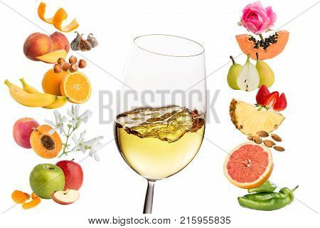 Macro close up of white wine glass surrounded by multiple fruits and flowers. Conceptual products representing wine aromas.Isolated on white background.
