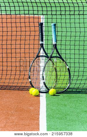 Two tennis racket and balls. Two tennis rackets leaning to tennis net.