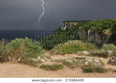 Thunderstorm is approaching over plateau of Crimean mountains. The dividing line of solar weather and stormy weather in Crimea. Chufut-Kale mountain.