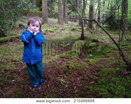 Scared boy in dark forest. Boy in coat lost alone in nature and frightened by fairy-tales. Lost kids in forest