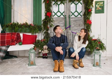Happy Beautiful Young Couple In Love Dressed In Sweater Sitting On Porch Steps At Light House With D