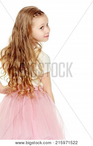Beautiful little blonde girl with long hair.In a lush short pink skirt and white T-shirt.Turning his back to the camera.Isolated on white background.