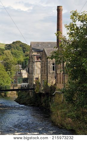 hebden bridge with view of the river calder with stone terraced houses and mill chimney