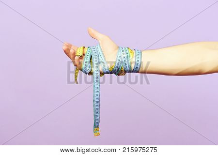 Mans Wrist Wrapped With Cyan And Yellow Measuring Tapes