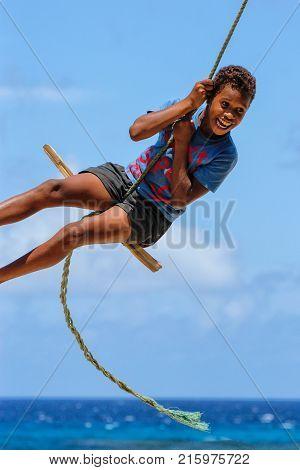 Lavena, Fiji - November 27: Unidentified Boy Swings On A Rope Swing On November 27, 2013 In Lavena V