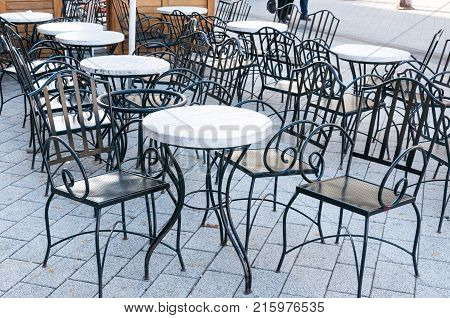 Empty black metal tables and chairs of coffee shop on the street selective focus