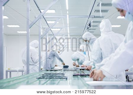 factory workers in white lab suits and face masks, producing tv sets on a green assembly line with some modern equipment
