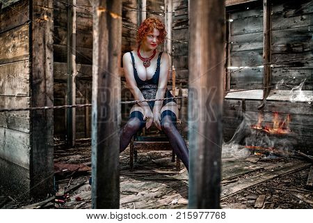 Beautiful red-haired woman with big breasts sitting in a negligee in a dirty room on a chair