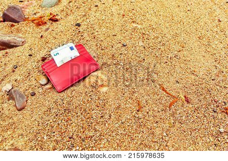 The lost purse on the seashore. The sandy beach a small red purse with the note of five euros
