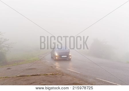 The car on the road in dense fog. Dense fog over the wet asphalted road in cloudy summer day the car goes with the lit headlights