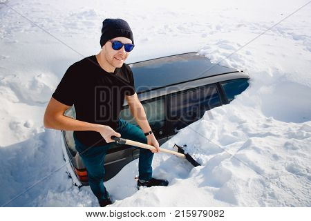 Man cleans snow and cleans car shovel from snow strong blizzard and hurricane.