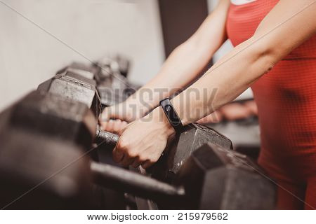 fitness bracelet and dumbbells. A girl with a bracelet takes a dumbbell in the hand standing in a row. The concept of technology sports and health to measure the pulse.