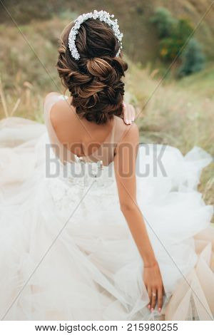 Bride In Wedding Dress Sitting On A Hill.