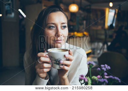 Close-up of pretty woman drinking cup of coffee in autumn / winter evening day. Morning drinking coffee and eating dessert. Relaxing mood break time