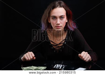 European girl drug addict in a black sweater and with purple hair looks sullen look and sits at the table with a dosed cocaine next to the Dolar bills. On a black background.