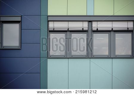 The modern facade of an office building with window rows and metal blinds.