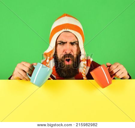 Man In Warm Hat Holds Cyan And Orange Cups