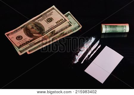 Several dosage strips of a cocaine drug, next to a white card, a bill twisted in a tube and a few dollar bills. On a black background.