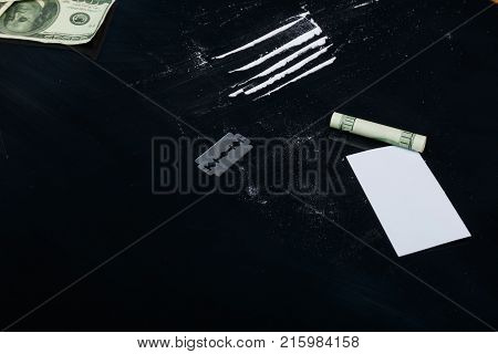 On a black background, dosed cocaine, a blade, a twisted dollar bill and a white card.