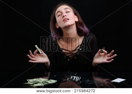 A drug-dependent young girl sniffs cocaine and throws her head back from enjoyment, holding a twisted bank note in her hand. On a black background.