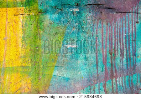 Close-up of abstract dirty painted wooden surface, flowing paint of blue, pink, yellow, green bright colors, as graffiti. Colorful grunge texture of wall. Abstract modern background, pattern, wallpaper, banner design