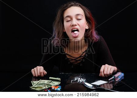 A drug-dependent young girl swallows a large white narcotic pill. Next to the table are scattered cocaine powder, dollar bills and two syringes. On a black background.