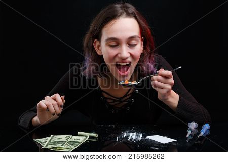 A drug addict young girl with colored hair swallows a bunch of narcotic tablets from a spoon. On the table there is a scattered powder of cocaine, dollar bills and a few syringes. On a black background.