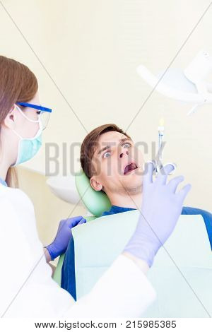 Frightened scared man male patient in dentist chair by dentist woman female in white medical gown mask and glasses with syringe. Humor concept