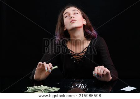 Young drug-dependent girl of European appearance under the influence of cocaine. Next to the table are scattered cocaine and cocoa dollies. On a black background.