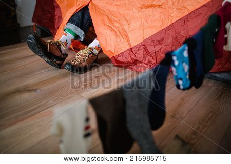 Feet in happy socks. Man is relaxing near tent and warming up his feet in happy socks. Close up on feet. Winter and Christmas holidays concept.