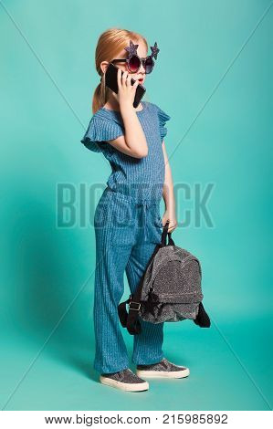 isolated on blue, red-haired girl in star-shaped sunglasses, blue overall and silver slip ons, holding a lustrous backpack and talking over the black cellphone. copyspace.