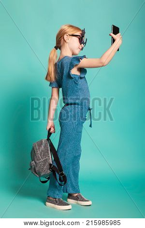 isolated on blue, red-haired girl in star-shaped sunglasses, blue overall and silver slip ons, holding a lustrous backpack and making selfie. copyspace.