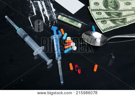 On a black background, two syringes, colored pills, dosed cocaine powder and dollar bills.