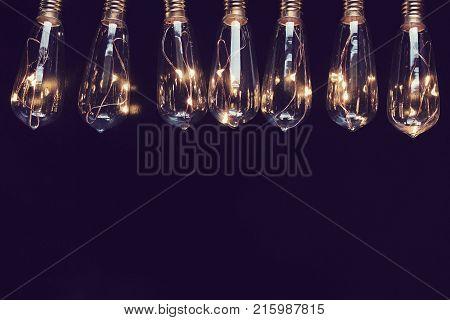 Incandescent filament style light bulbs frame black background.