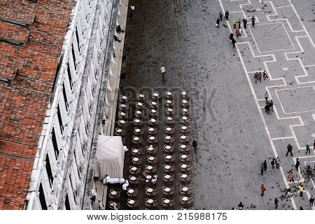 Venice Italy. April 20 2012: view to San Marco Square from the tower pedestrian zone people walking restaurant and tables prepared for dinner.