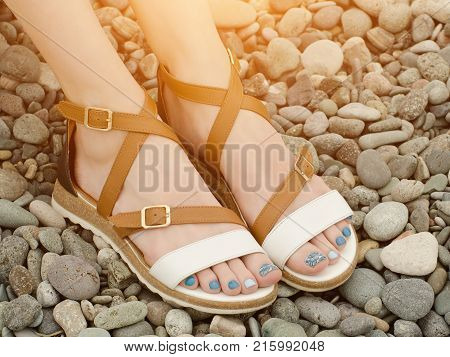 Female feet in sandals pebbles close up