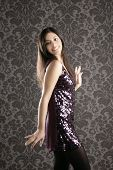 elegant fashion woman with night purple sequins dress dancing in wallpaper background poster