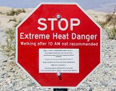 arid scenery including a heat warning sign at Death Valley National Park in USA poster