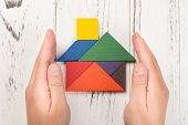 hands surround a wooden house made by tangram home insurance concept or representing home ownership poster