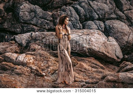 Beautiful Young Boho Style Woman On Stones Background At Sunset