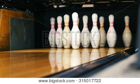 Close-up View Of White Pins Standing In Th End Of Bowling Alley Lane And Rolling Bowling Ball In A S