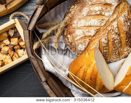 Breads In Baskets, Variety Baking Products On Wooden Surface
