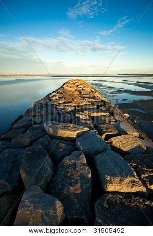 A long stone jetty stretches toward the horizon on the historic Ottawa River near Britannia beach. poster