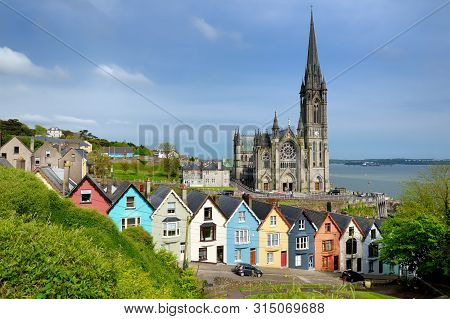 Colorful Row Houses With St. Colman's Cathedral In Background In The Port Town Of Cobh, County Cork,