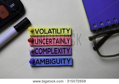 Volatility Uncertainly Complexity Ambiguity - VUCA text on sticky notes isolated on office desk poster