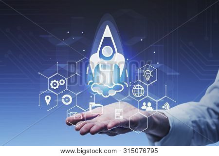 Hand Of Man In White Shirt Launching Startup Rocket Hologram. Concept Of Starting Your Business And