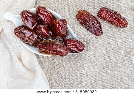 Close-up Of Juicy Dates (fruit). On Delicate Cloth And Rustic Look.